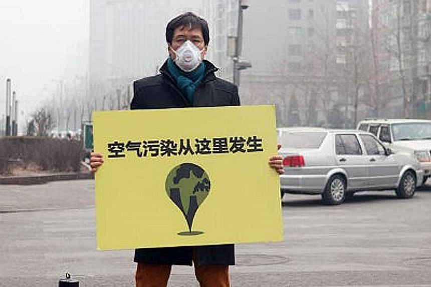 """Mr Quek holding up a sign which says """"Air Pollution Comes From Here"""" in Beijing in 2014. Debunking the stereotype of a strident agitator, Mr Quek speaks in the measured tones of a thinker. He is the go-to person for researchers, investors and policym"""