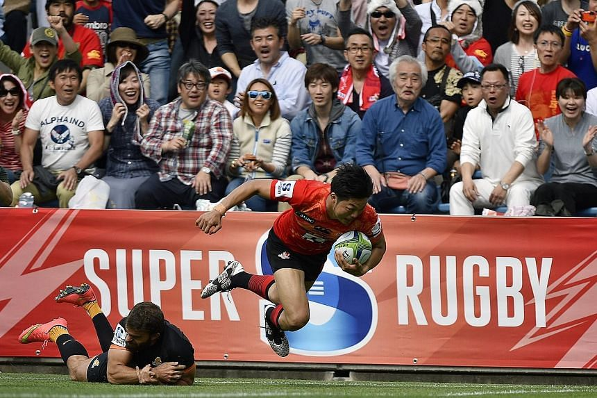 Yasutaka Sasakura (left) scoring the first of the Sunwolves' three tries against the Jaguares in their Super Rugby match at the Prince Chichibu Memorial Stadium in Tokyo yesterday, while the team (above) celebrate their maiden victory.