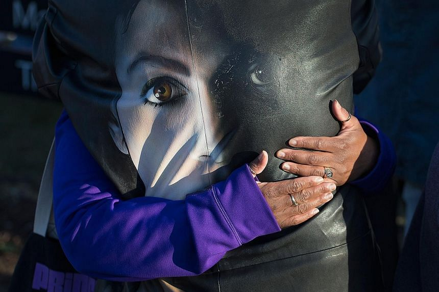Music fans comfort each other while visiting a memorial outside Paisley Park, the home and studio of Prince, in Minnesota on Friday.