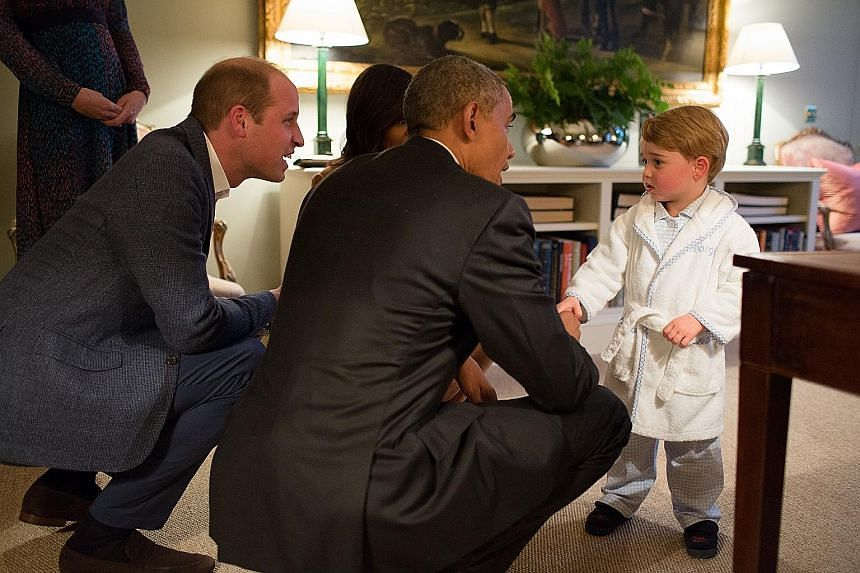 Left: A photo released by Kensington Palace on Friday shows Britain's Prince George of Cambridge (at right) meeting US President Barack Obama and First Lady Michelle Obama (partly hidden) at Kensington Palace in London, while the young royal's father