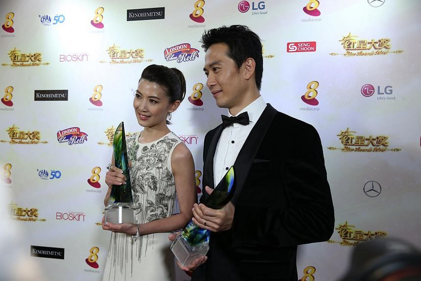 Best Actor Qi Yuwu and Best Actress Jeanette Aw posing with their awards at the Star Awards on Sunday (April 24).