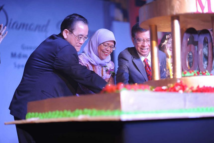 (From left) Dr Eric Kuan, Mdm Halimah Yacob and Dr Ahmad Magad (Senate Chairman of MDIS) cutting the birthday cake to mark MDIS' 60th anniversary.