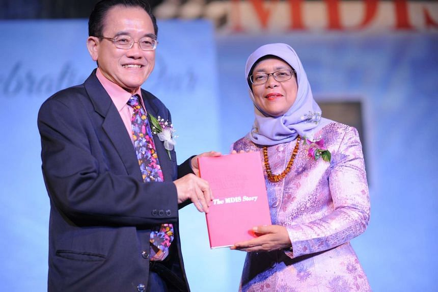 "Dr Eric Kuan presents a copy of the commemorative book, ""Inspiring Lifelong Learning, The MDIS Story"" to Mdm Halimah Yacob."