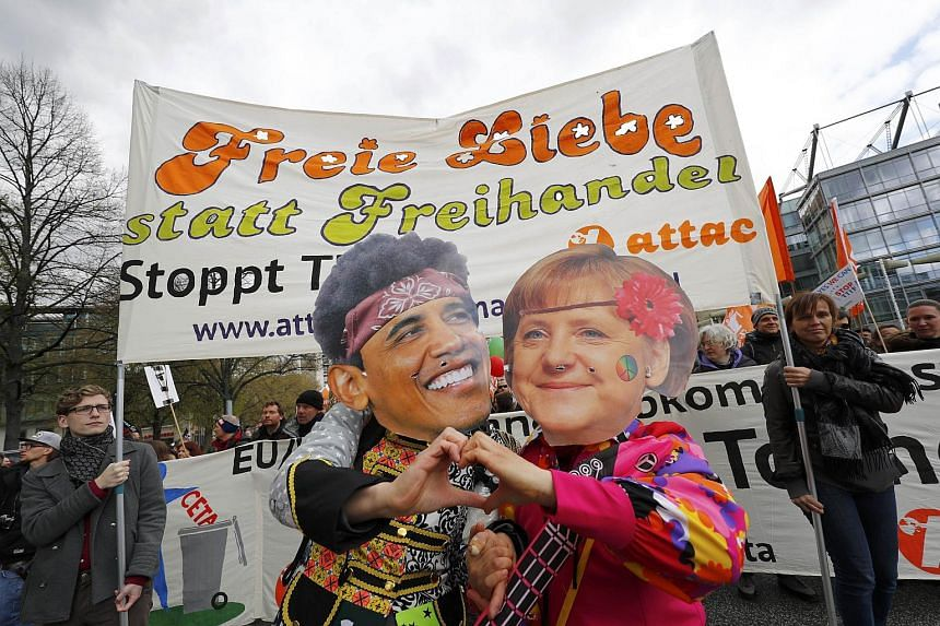Protesters wearing masks depicting German Chancellor Angela Merkel and US President Barack Obama, demonstrating against the TTIP agreement ahead of Obama's visit in Hanover, on April 23, 2016.