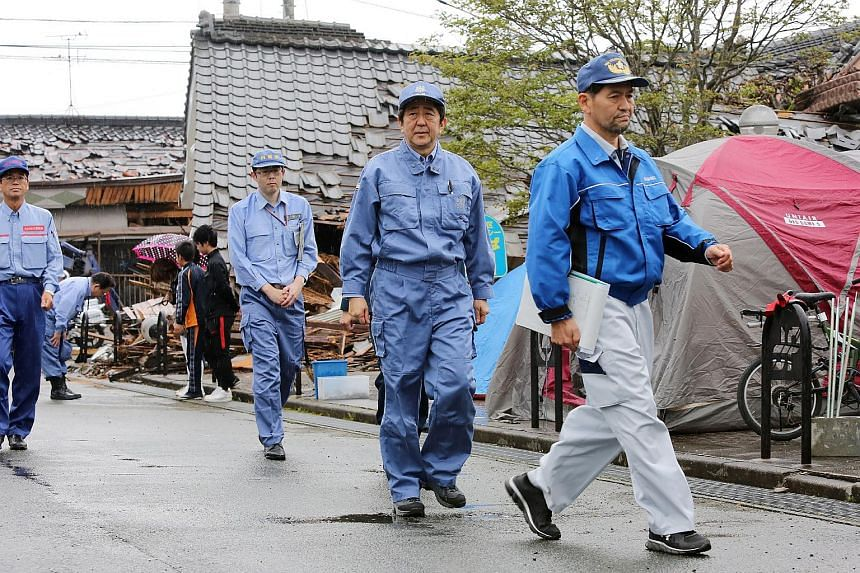 Japanese Prime Minister Shinzo Abe (centre) visits a earthquake affected area in Mashiki, Kumamoto prefecture, on April 23, 2016.