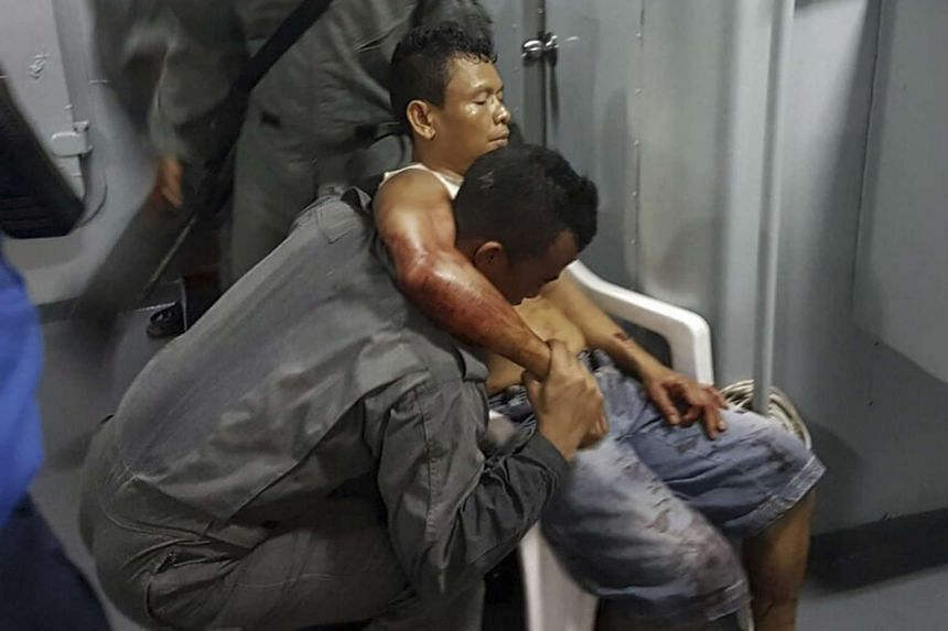 A member of the Malaysian Maritime Enforcement Force helping an injured shot Indonesian sailor (right) after their ship was hijacked by a pirate group allegedly linked with Abu Sayyaf on April 25, 2016.