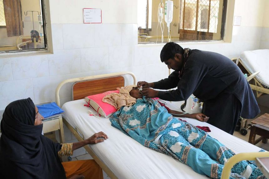 A woman receives medical treatment at a local hospital in Layyah, after eating poisonous sweets, on April 23, 2016.