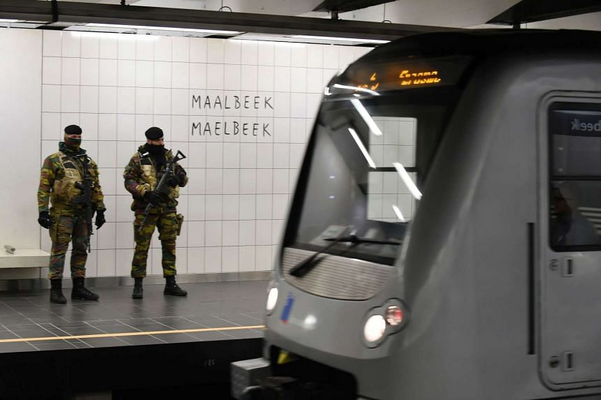 Belgian servicemen stand guard as a train arrives at the Maalbeek metro station.