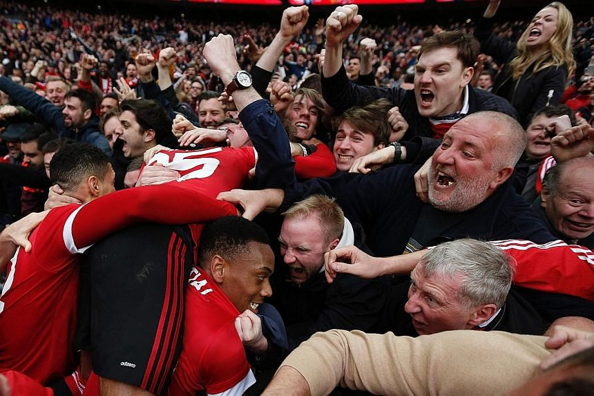Almost engulfed by a sea of jubilant Manchester United supporters, striker Anthony Martial celebrates after scoring the 93rd-minute winning goal at Wembley in the dramatic 2-1 victory against Everton on Saturday to put his team into the FA Cup final.