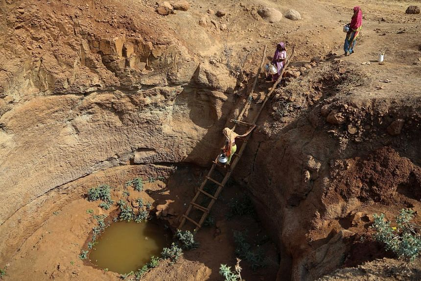 Villagers collecting water from an almost dried-up well in Mhaismal village in Nashik district of the Indian state of Maharashtra last week. A prolonged drought has raised the spectre of a rise in farmer suicides in the state, where around nine farme