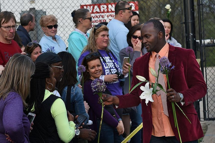 A staff member handing out flowers to fans from a memorial service held inside Prince's Paisley Park compound in Minneapolis.