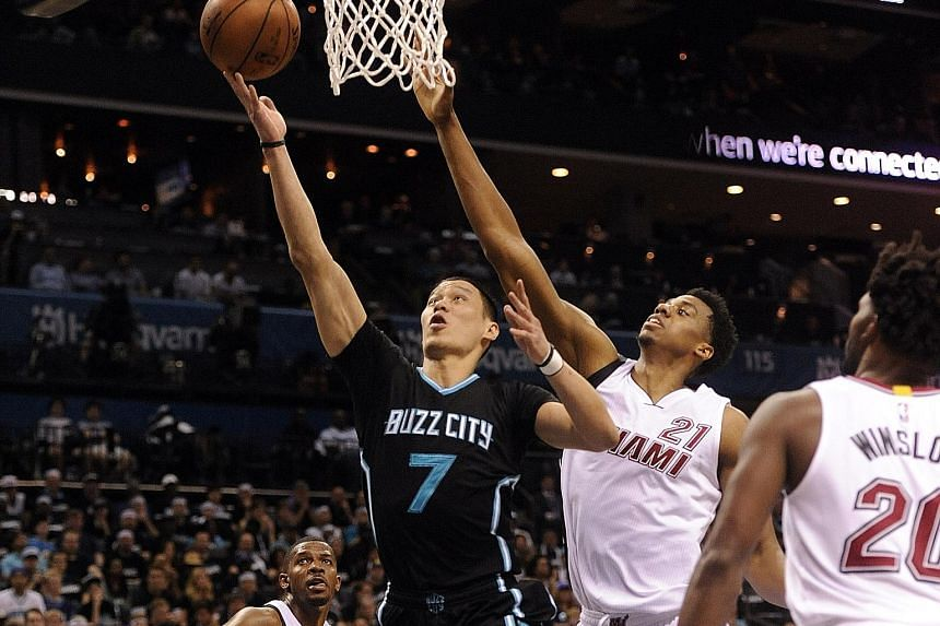 Charlotte Hornets guard Jeremy Lin drives past Miami Heat's Hassan Whiteside (21) for a lay-up during Game Three of their first round play-off series at the Time Warner Cable Arena. The Hornets' 96-80 win over the Heat was their first post-season win