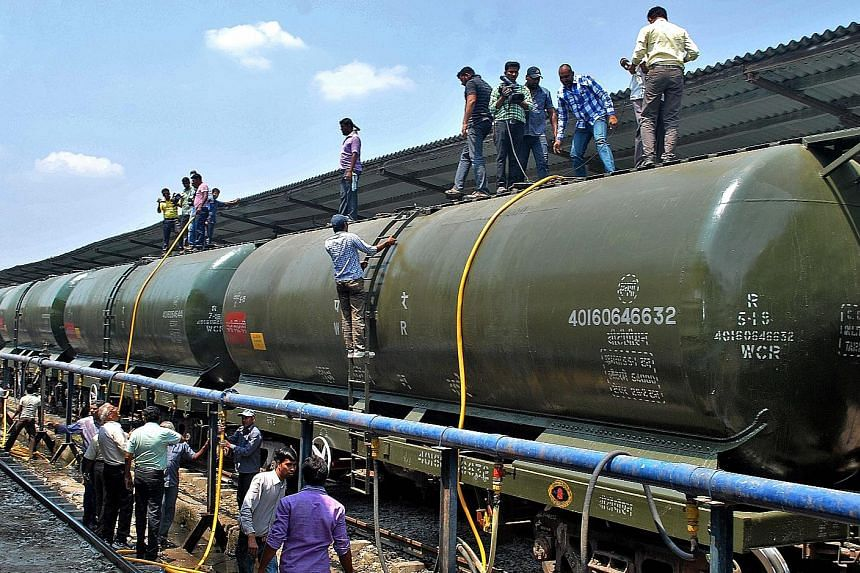 Villagers trying to draw water from an almost dried-up well (above) at Rasegaon in Maharashtra. Elsewhere in the state, workers at a railway station in Miraj city (left) load water onto a train bound for drought-hit areas in and around Latur district