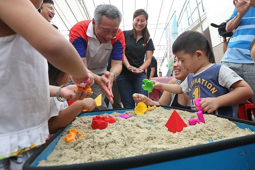 Mr Lee with young children at a sand box in Teck Ghee Community Club yesterday. The Prime Minister was happy to learn that a Healthy Baby contest held there attracted 145 baby contestants, almost double the number of participants last year.