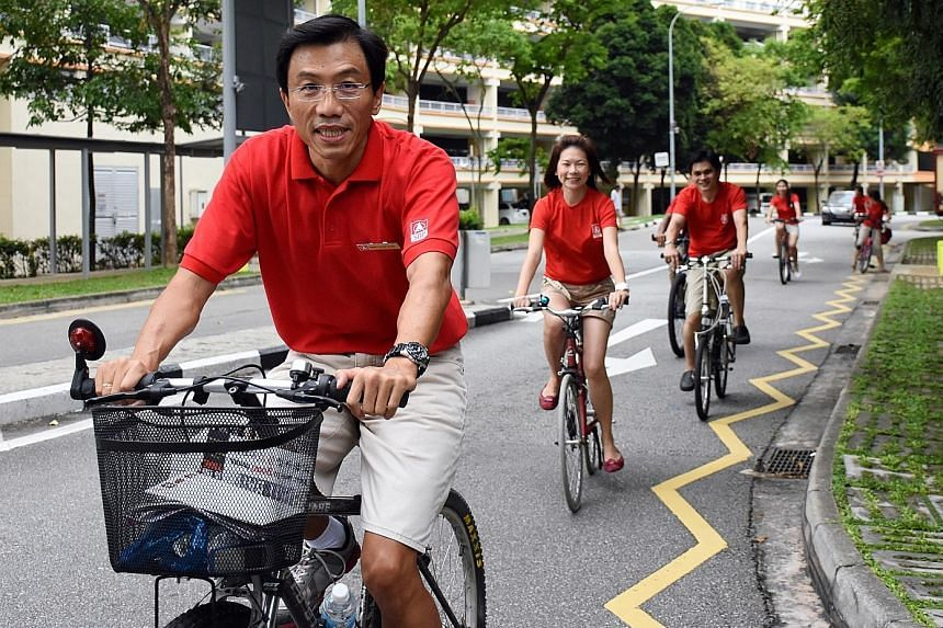 """Dr Chee cycling with his team in Bukit Batok yesterday morning. The SDP chief described Bukit Batok as a seat that is """"going to be like our first-born after a long absence"""". Mr Murali speaking to people in Bukit Batok yesterday. He was accompanied by"""