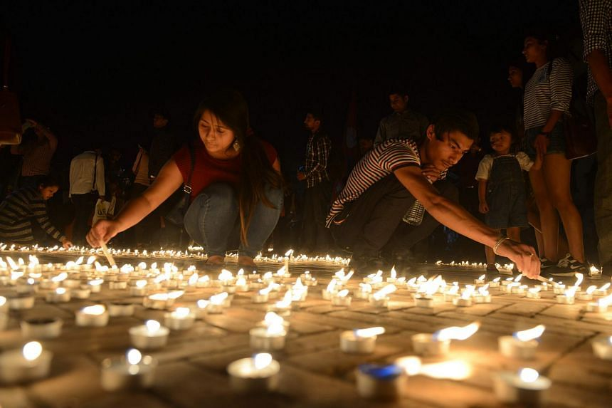 Nepalese residents gather to light candles during a vigil to mark the first anniversary of the earthquake in Durbar Square in Kathmandu, on April 24, 2016.