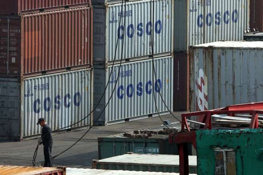 A dock worker working near Cosco containers in Victoria Harbor in Hong Kong.