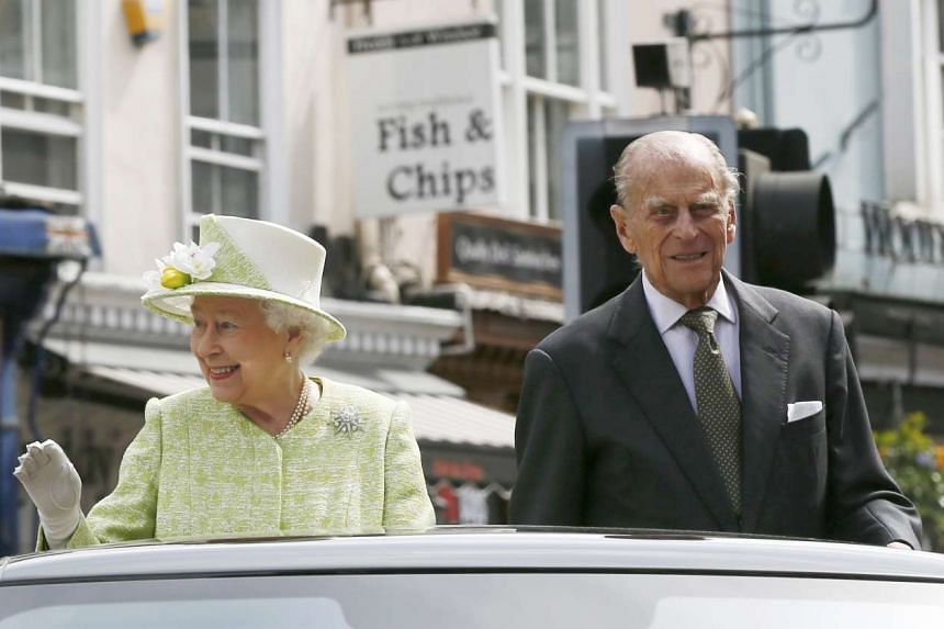 Britain's Queen Elizabeth waves to well wishers as she is driven with Prince Philip on her 90th birthday on Thursday (April 21).