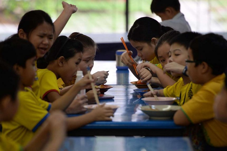 Damai Primary School pupils having their meals at the school canteen.