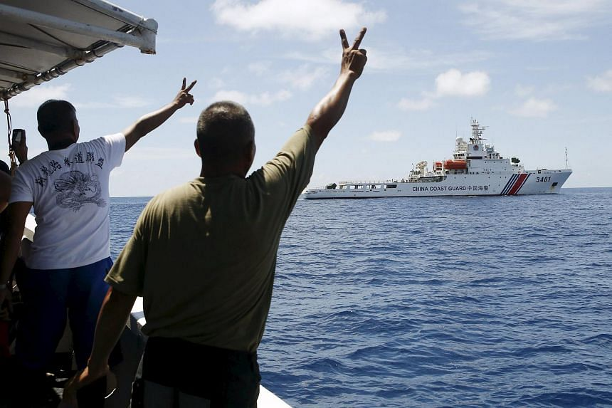 Filipino soldiers gesture at a Chinese Coast Guard vessel on the disputed Second Thomas Shoal, in the South China Sea, on March 29, 2014.