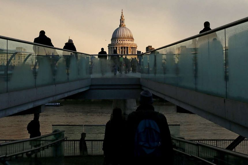 City workers walking towards St Paul's Cathedral as they cross the Millennium footbridge during sunrise in central London, Britain, on Jan 14, 2016.