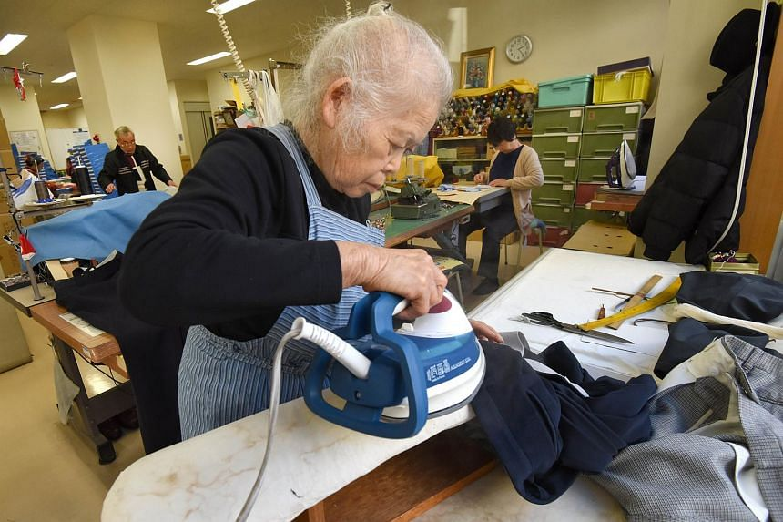 Workers repair clothes at a seniors' work centre in Tokyo, on Dec 18, 2015.