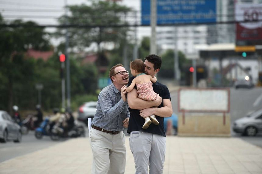 American Gordon Lake (left) and his Spanish husband Manuel Valero (right) play with their daughter Carmen in Bangkok, on March 30, 2016.