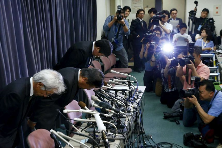 Mitsubishi Motors Corp's president Tetsuro Aikawa (centre) bows with other company executives at a news conference at the company's headquarters in Tokyo, Japan, on April 26, 2016.