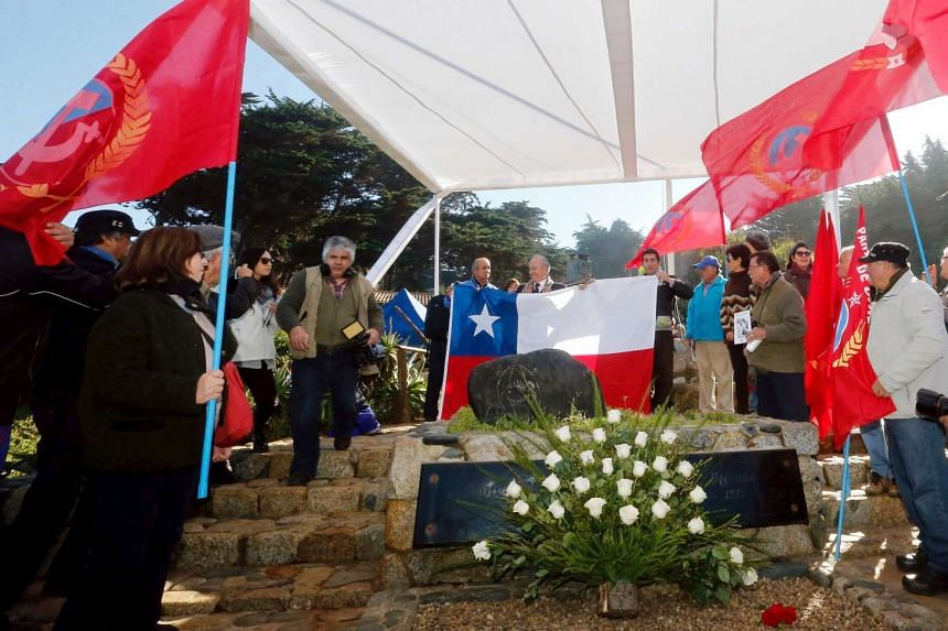 Members of the communist party give honors next to the tomb of Chilean poet and Nobel laureate Pablo Neruda during the reburial of his remains inside of his house-museum in Isla Negra city, Chile, on April 26, 2016.