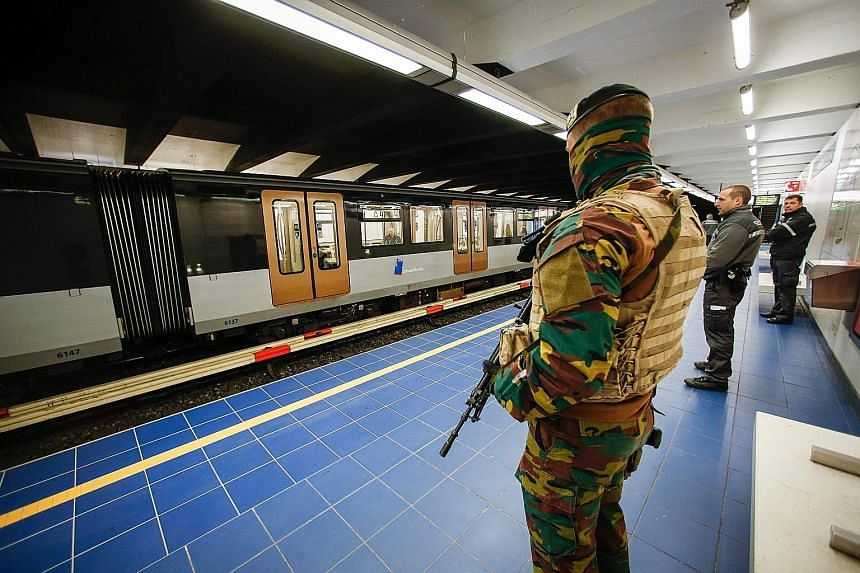 A Belgian soldier standing guard as a train arrives at the Maelbeek metro station in Brussels yesterday. It was the station's first day of operation since being closed following the terror attacks in the city on March 22. The station and the city's a