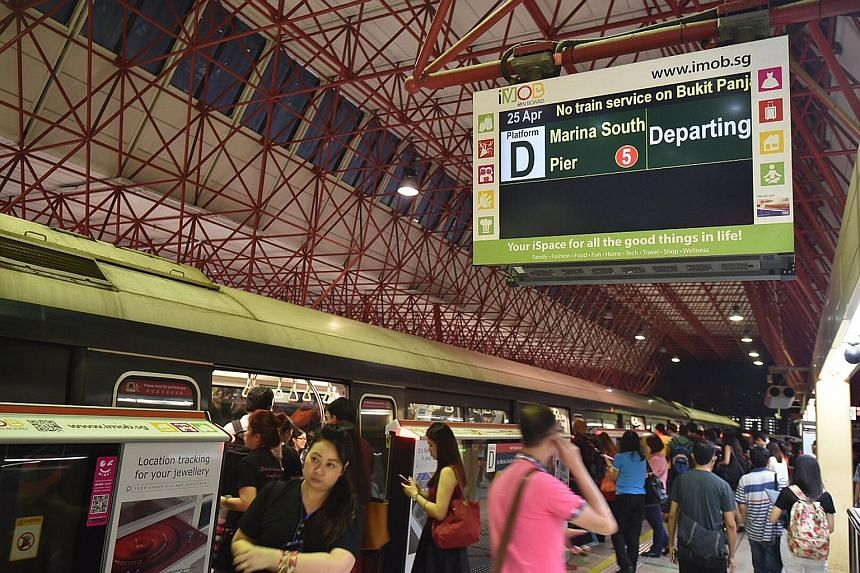 Commuters on the platform at Jurong East MRT station last night. The screen shows a notice about the disruption in train service. The Tiong Bahru MRT station with its emergency lights on as many passengers waited in the train for service to resume.
