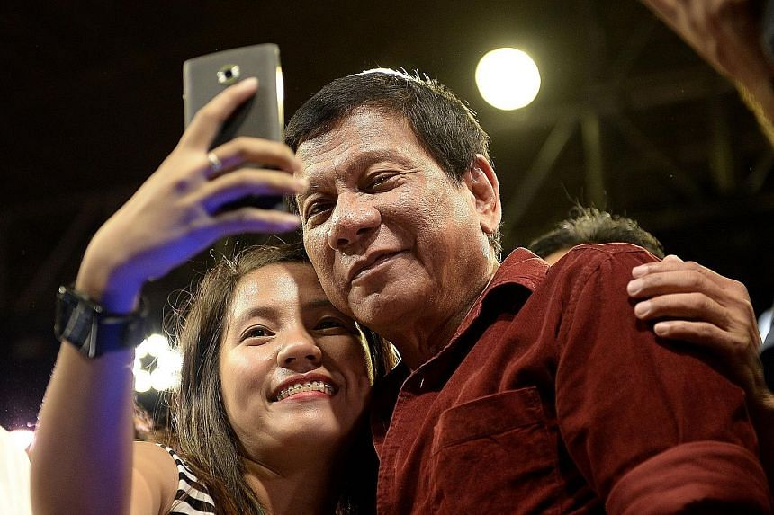 A supporter taking a selfie with Davao mayor and presidential candidate Rodrigo Duterte, 71. Mr Duterte has promised to wipe out drugs, crime and graft within six months, if elected president in the May 9 polls.
