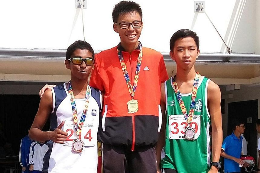 Fang Yiyang (centre) of Commonwealth Secondary School stands with St Joseph's Institution's Dave Tung and Guangyang Secondary School's Ruben Loganathan on the podium after winning the 2000m steeplechase.