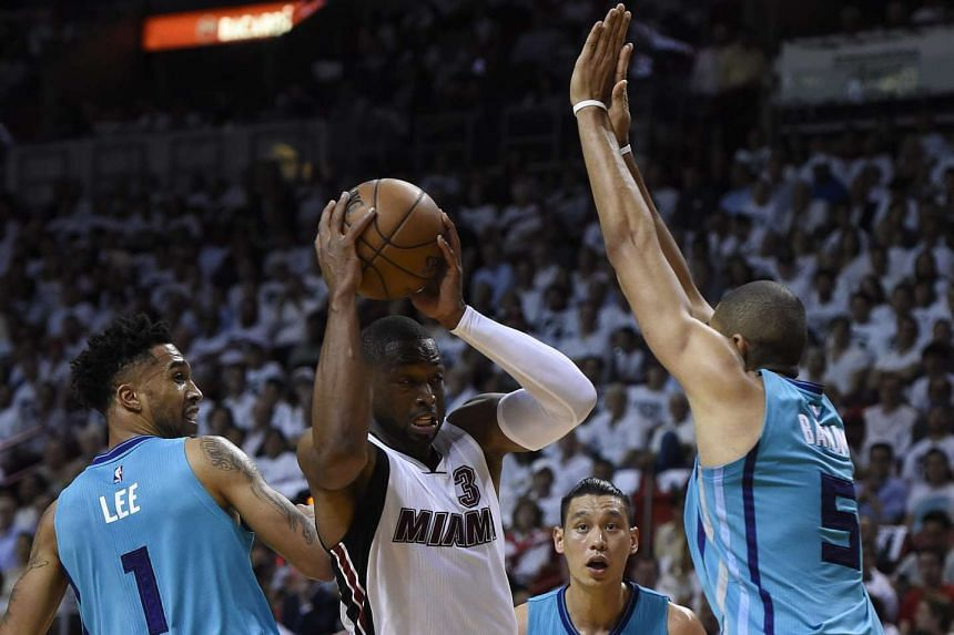Miami Heat guard Dwyane Wade (second from the left) is guarded by Charlotte Hornets (left-right) Courtney Lee, Jeremy Lin and Nicolas Bantum during the game, on April 20, 2016.