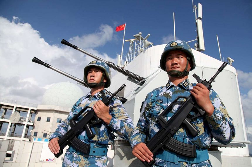 Soldiers of China's People's Liberation Army Navy stand guard in the Spratly Islands, known in China as the Nansha Islands, on Feb 10, 2016.