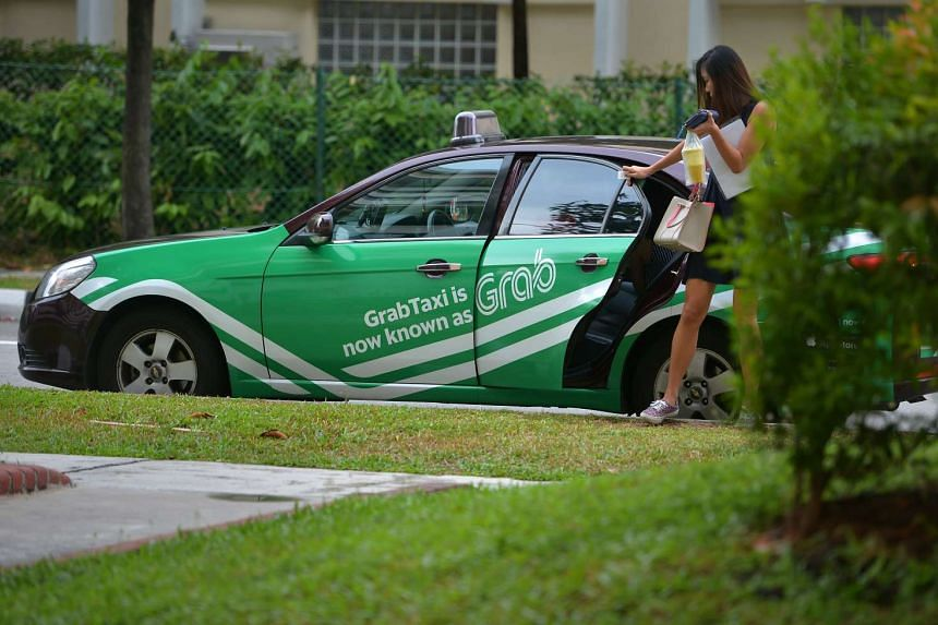 A passenger getting out of a taxi with Grab advertisemnet decal pasted on it.