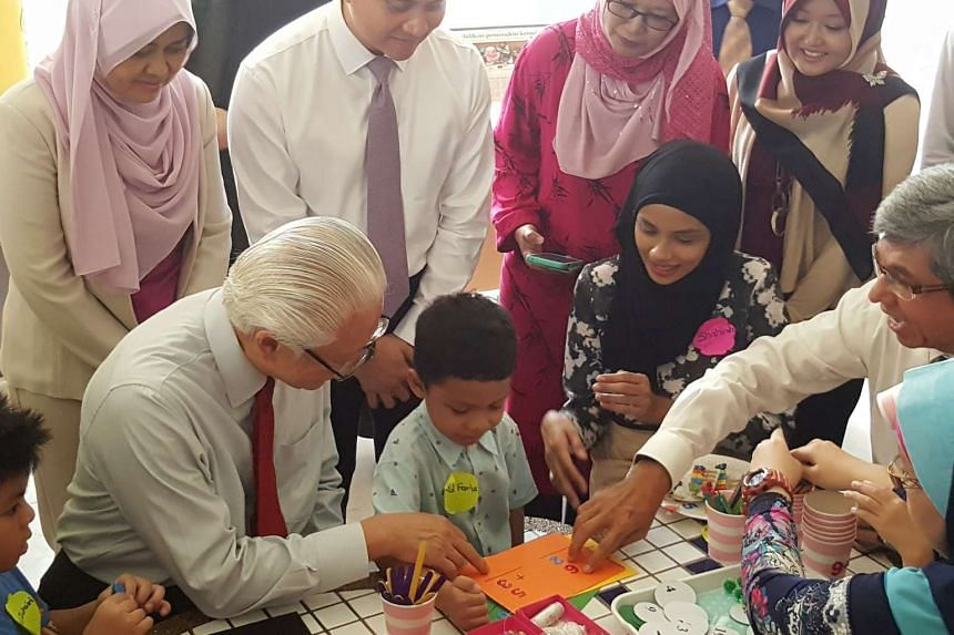 President Tony Tan Keng Yam (left) and Minister-in-charge of Muslim Affairs Dr Yaacob Ibrahim (right) interacting with Mendaki beneficiaries at a Mendaki satellite centre in Pasir Ris on April 26, 2016.