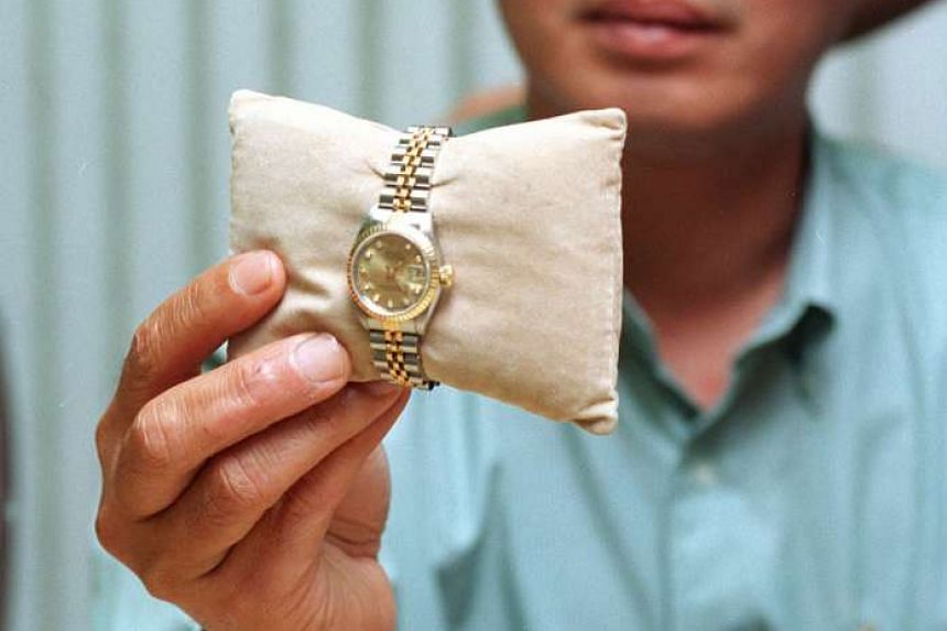 A police officer holding the watch for which Jonaris killed Madam Poh.