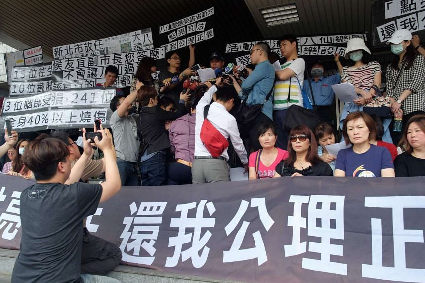 Relatives of water park explosion victims display placards calling for justice and for the New Taipei City government to take their responsibilities for the accident, in Taipei, on April 26, 2016.