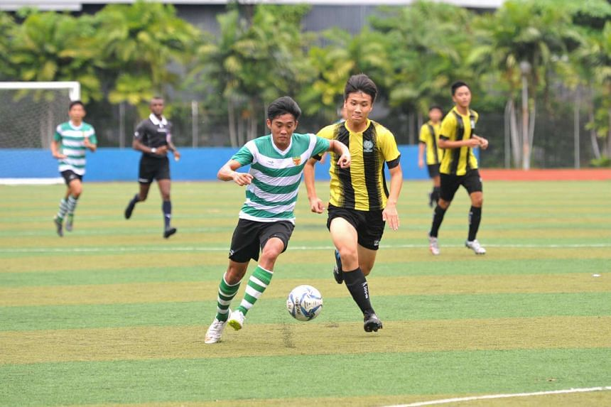 Raffles Institution's Jonathan Chua (left) running with the ball against opposing Temasek Junior College players.