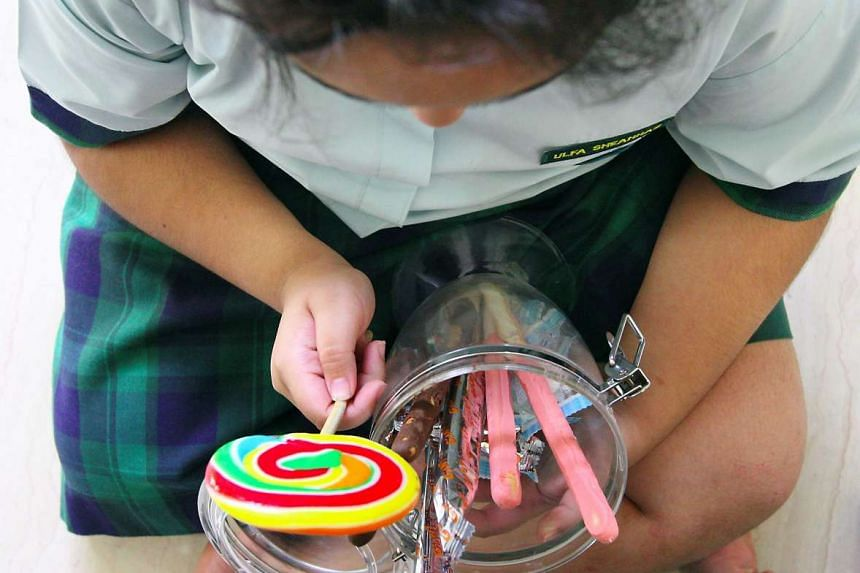 An obese child holding onto a jar of sweets and snacks.