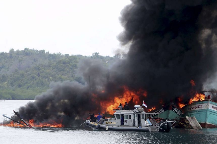 An Indonesian police boat near Malaysian and Vietnamese fishing boats as they are destroyed for illegal fishing in Batam, Riau Islands on April 5, 2016.