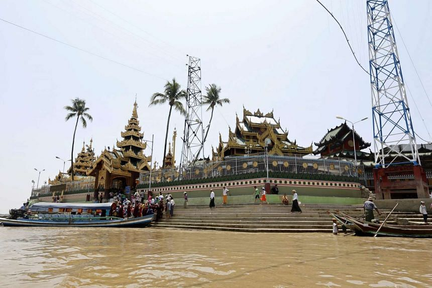 People cross the river by boat to visit the KyaikMhawWynn pagoda in ThanLyin, on the outskirts of Yangon, Myanmar on April 19, 2016.