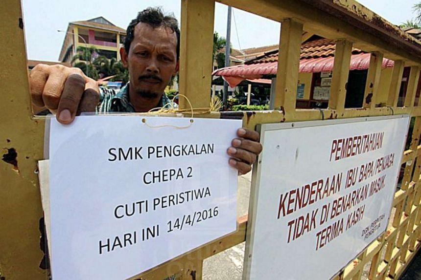 A staff member of SMK Pengkalan Chepa 2, a secondary school in Kelantan, Malaysia, indicates the school is closed on April 21, 2016.