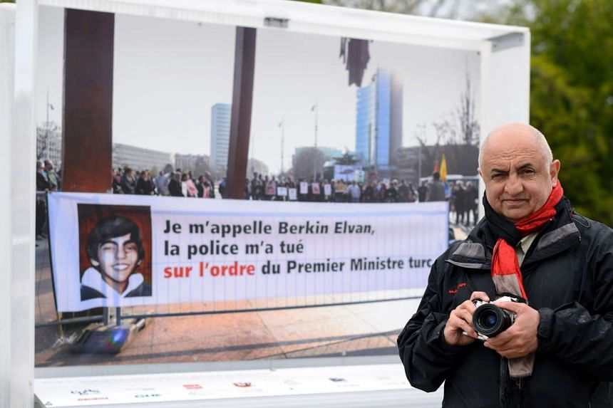 Photographer Demir Sonmez poses in front of his picture, taken during a demonstration on March 14, 2014 and showing a banner in support of teenager Berkin Elvan.