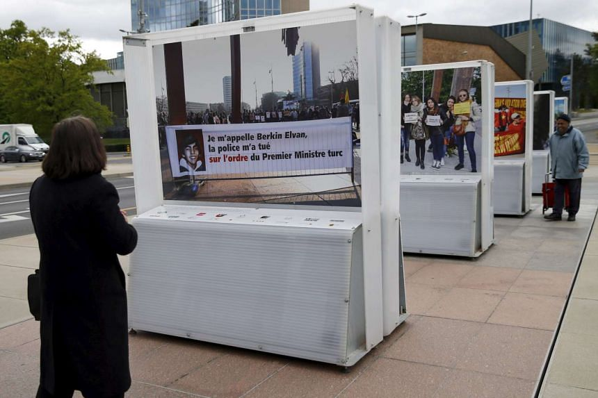 A visitor looks at a picture by photographer Demir Sonmez, showing a banner in support of teenager Berkin Elvan, during an exhibition on the Place des Nations in Geneva, Switzerland, on April 26, 2016.