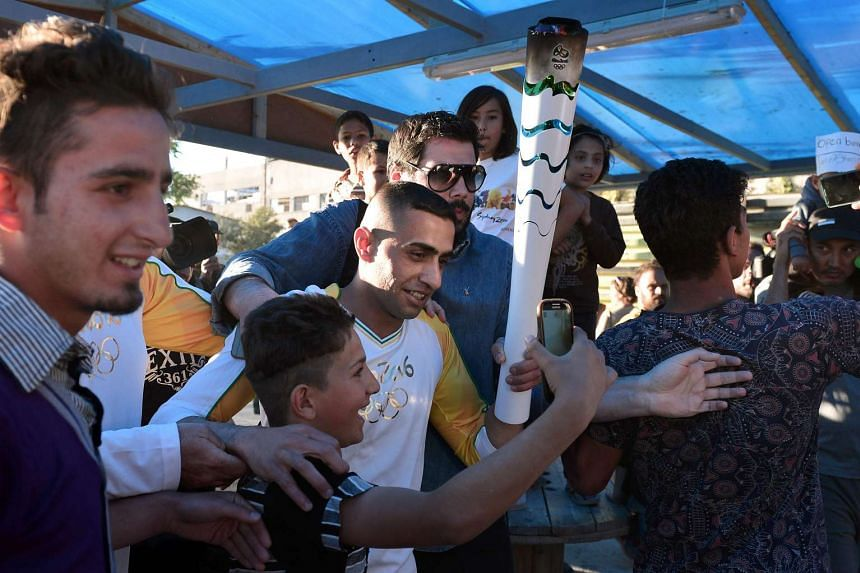 Syrian refugee and amputee swimmer Ibrahim al-Hussein (C), 27, greets refugees as the Olympic Flame torch relay passes through the Eleonas refugee camp in Athens on April 26, 2016.