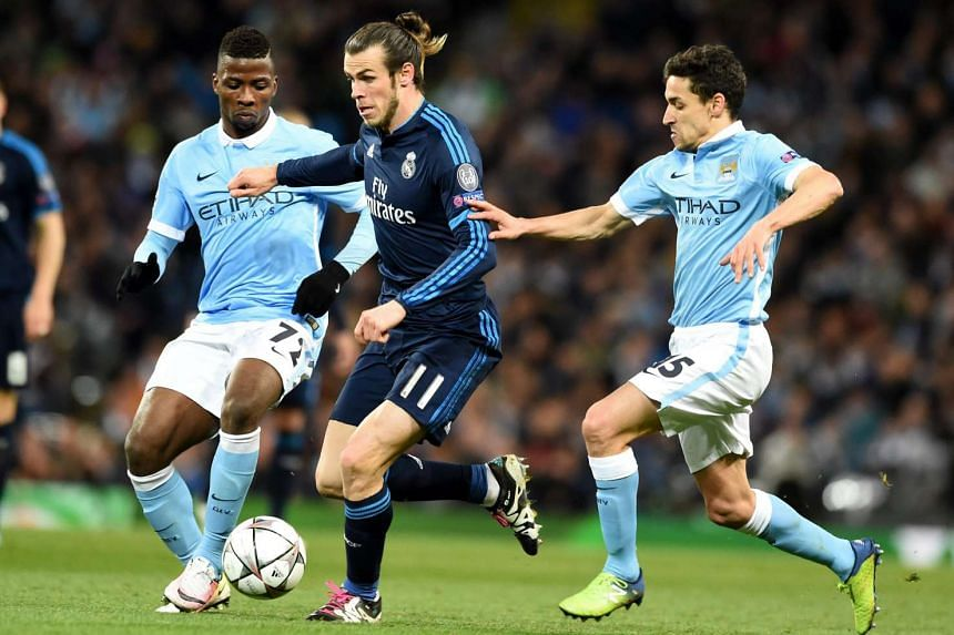 Gareth Bale of Real Madrid (centre) in action against Kelechi Iheanacho (left) and Jesus Navas of Mancester City (right) during the UEFA Champions League semi final first leg socer match at the Etihad Stadium in Manchester, Britain, on April 26, 2016