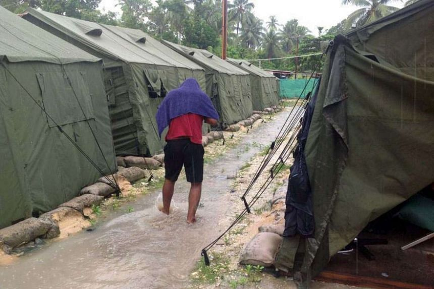An undated photo obtained on Feb 18, 2014 shows a man walking between tents at Australia's regional processing centre on Manus Island in Papua New Guinea.