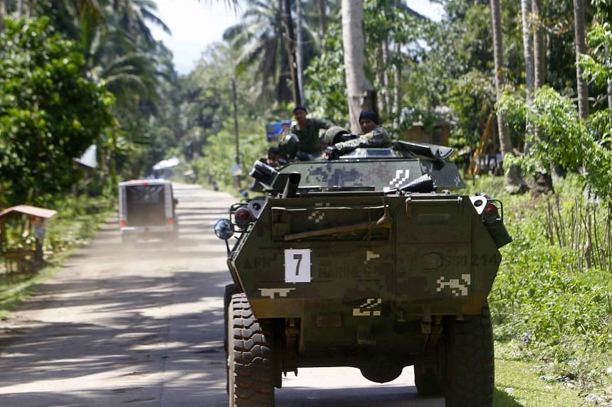 Filipino soldiers riding an armoured vehicle along a road on the outskirts of Jolo, Sulu Island, in the southern Philippines, on April 27, 2016.
